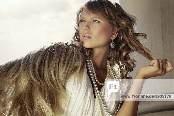 Portrait einer jungen blonden Frau im weißen Kleid mit Schulterschmuck und Perlenkette