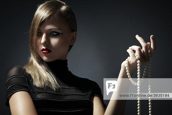 Jungen blonde Frau im schwarzen Kleid hält eine Perlenkette in ihrer Hand  Fashion