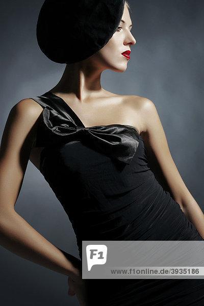 Seitliches Portrait einer jungen Frau im schwarzen Kleid und schwarzem Hut  Fashion