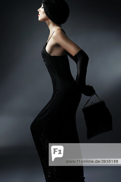 Seitliches Portrait einer jungen Frau im schwarzen Kleid mit schwarzem Hut  Handschuhen und Handtasche  Fashion