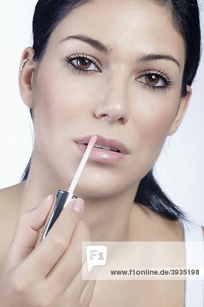 Junge Frau beim Auftragen von Lipgloss  direkter Blick  Beauty mund