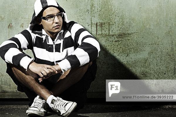 Portrait eines jungen Mannes mit Kapuzenjacke sitzend vor einem alten Stahltor  den Blick abgewandt  Jugendlicher  cool