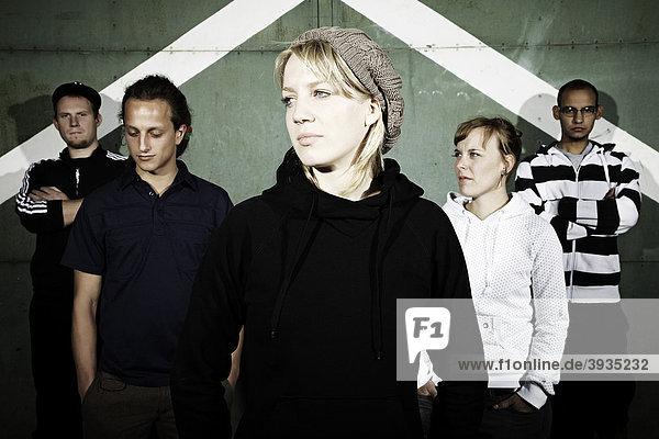 Portrait einer Jugendgruppe vor einem alten Stahltor  im Focus eine junge Frau mit Strickmütze  Jugendliche  Gruppe  cool