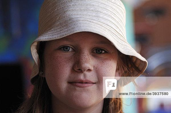 Portrait eines kleinen Mädchens mit Sommersprossen und mit weißem Hut