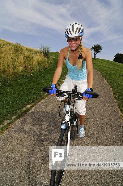 Junge Frau fährt Rad  Olympiagelände  München  Bayern  Deutschland  Europa