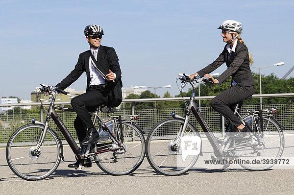 Geschäftsleute auf Elektrorädern  Pedelecs  Olympiagelände  München  Bayern  Deutschland  Europa