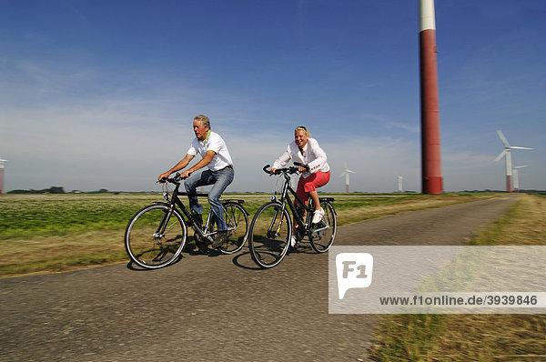 Radfahrer vor Windkraftanlagen  Sexbierum  Friesland  Holland  Niederlande  Europa