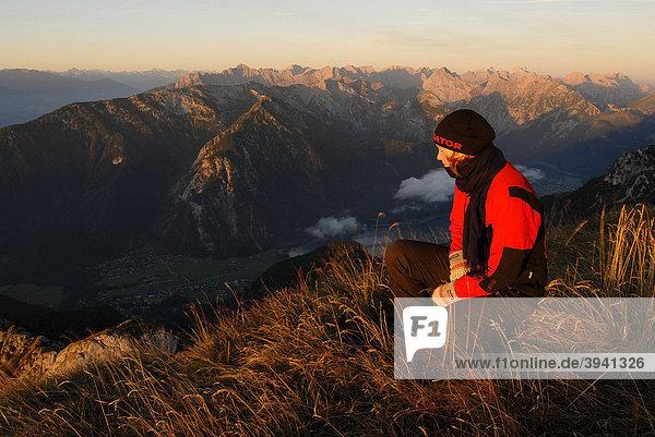 Junge Frau schaut von der Heidachstellwand,  2192m,  bei Sonnenaufgang,  Alpenglühen,  hinunter auf den Achensee mit Maurach,  Rofan,  Achensee,  Tirol,  Österreich,  Europa