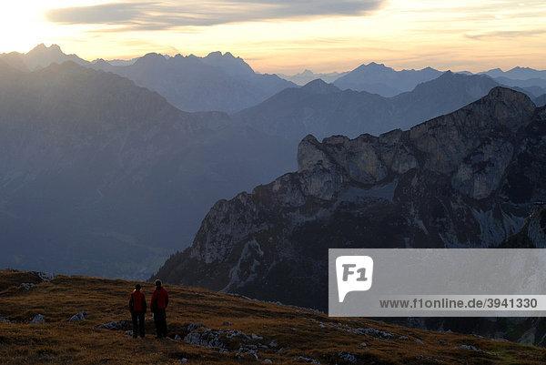 Junge Frau und Mann  Wanderer  schauen von der Heidachstellwand  2192m  in den Sonnenuntergang  Richtung Karwendel und Achensee mit Maurach  Rofan  Achensee  Tirol  Österreich  Europa