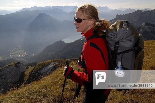Wanderin  junge Frau mit Tourenrucksack und Trekkingstöcken auf dem Gipfel der Heidachstellwand  2192m  mit Blick in das Inntal und an den Achensee mit Maurach und ins Karwendel  Rofan  Achensee  Tirol  Österreich  Europa