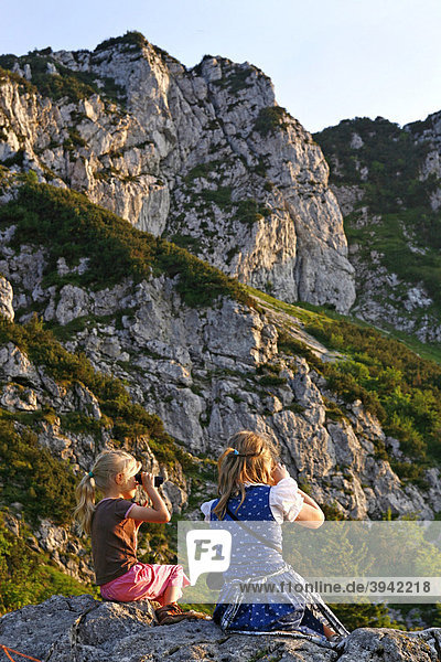 Mädchen schauen durch Fernglas an der Kampenwand  Chiemgau  Oberbayern  Bayern  Deutschland  Europa