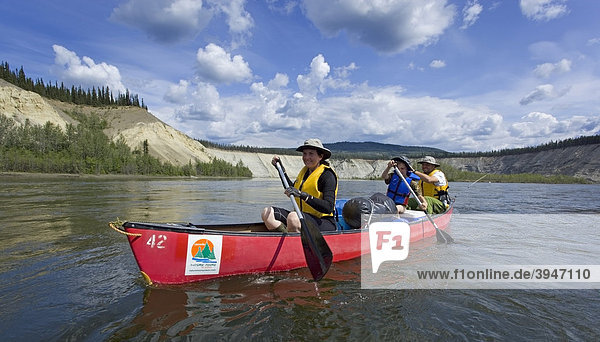 Eine Familie mit Sohn paddelt in einem Kanu auf dem Teslin River  dahinter die hohe Böschung des Flussufers  Yukon Territory  Kanada