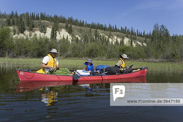 Familie mit Sohn in einem Kanu beim Angeln  Teslin River High  hohe Uferböschung  Yukon Territory  Kanada
