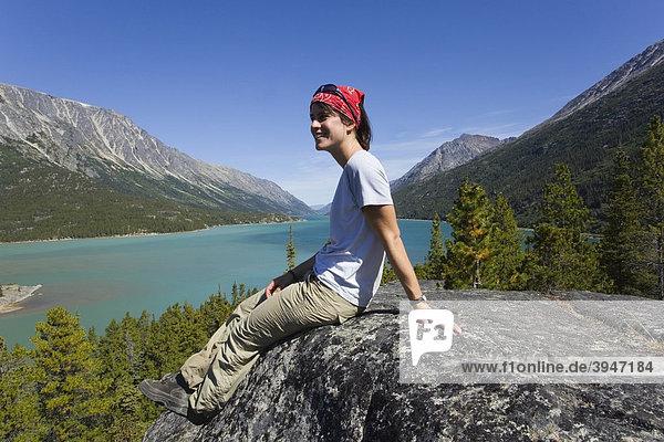 Junge Wanderin  Rucksacktourist  auf einem Felsen sitzend  ruht aus und genießt die Aussicht auf den Lake Bennett See  historischer Chilkoot Pass  Chilkoot Trail Wanderweg  Yukon Territory  British Columbia  BC  Kanada