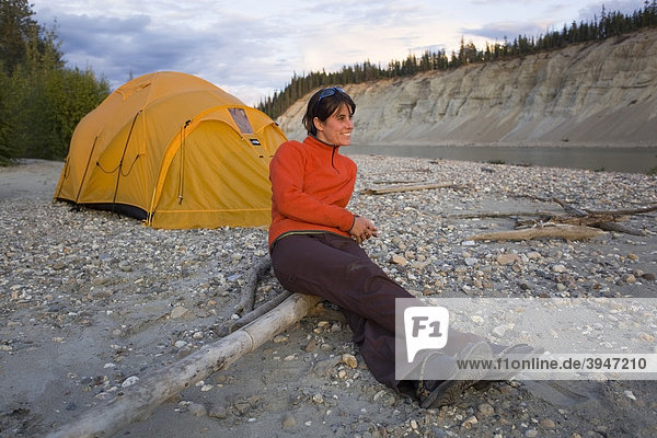 Young woman sitting  enjoying view  relaxing  tent  high cut bank  river cliff  erosion  behind  upper Liard River  Yukon Territory  Canada
