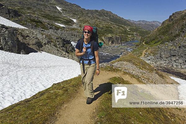 Junge Wanderin  Rucksacktour  historischer Chilkoot Pass  Chilkoot Trail Wanderweg  Schneefeld dahinter  alpine Tundra  Yukon Territory  British Columbia  BC  Kanada