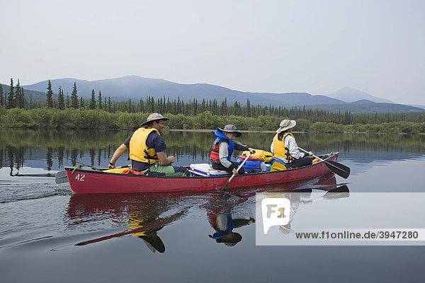 Familie mit kleinem Jungen in einem Kanu  paddeln  Kanufahren  Spiegelung auf dem ruhigen Teslin River  Yukon Territory  Kanada