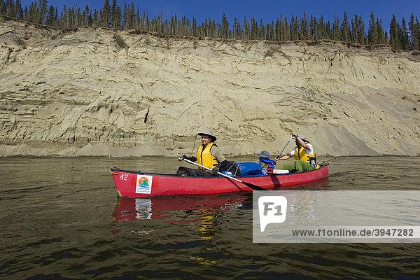 Familie mit kleinem Jungen in einem Kanu  paddeln  Kanufahren auf dem Teslin River  hoher Prallhang  hinten Erosion  Yukon Territory  Kanada