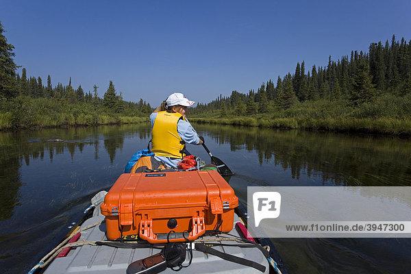 Junge Frau sitzt  paddelt im Kanu  oberer Liard River  Yukon Territory  Kanada