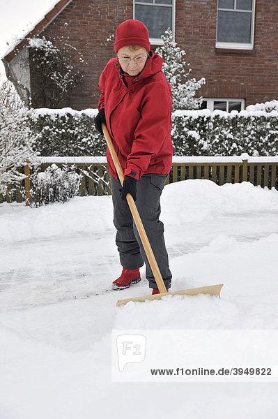Frau räumt Schnee