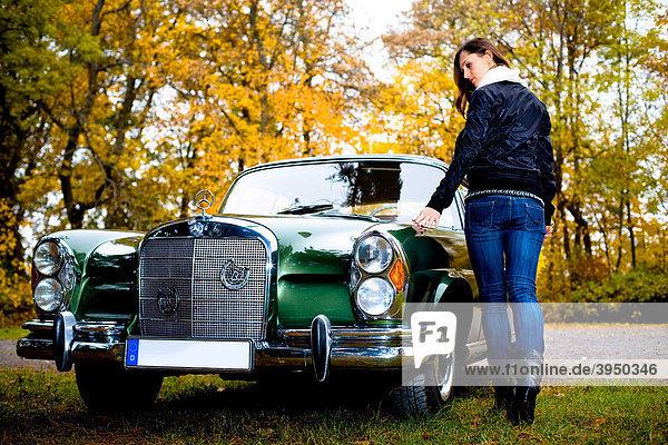 Junge Frau am Oldtimer-Modell MB 220 SE Cabrio Bj. 1964