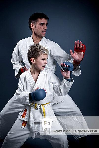 Junge und Trainer in Karatepose