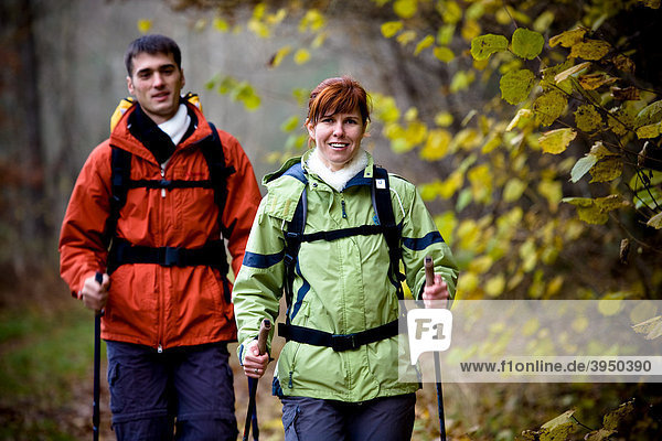 Couple hiking through a forest in autumn