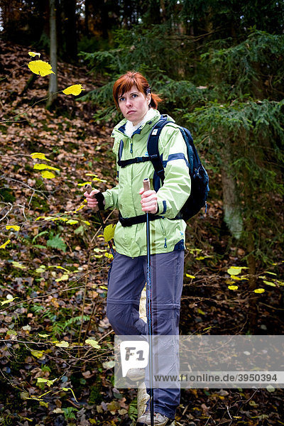 Woman hiking through a forest in autumn