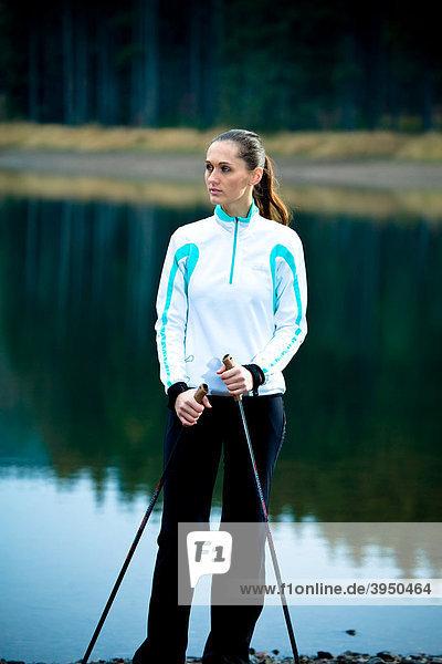 Junge Frau macht Pause bei einer Wanderung am See