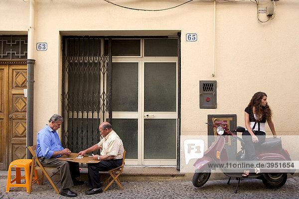 Straßenszene  Männer spielen Karten  Mädchen sitzt auf Vespa  Cefalu  Provinz Palermo  Sizilien  Italien  Europa
