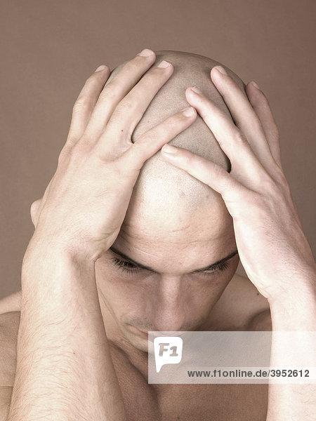 Mann  glatzköpfig  Kopf  festhalten