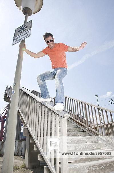 Junger Mann rutscht auf dem Geländer einer Fußgängerbrücke