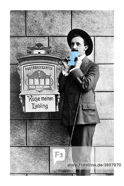 Mann küsst hellblauen Liebesbrief vor Briefkasten  Küsse meinen Liebling  Valentinstag  Postkartenmotiv  um 1900