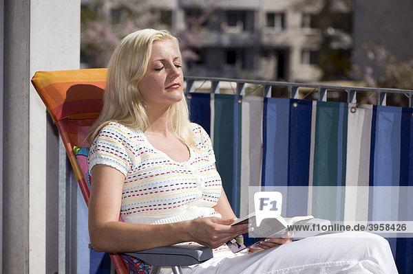 Junge Frau auf einem Balkon  lesend  sonnend