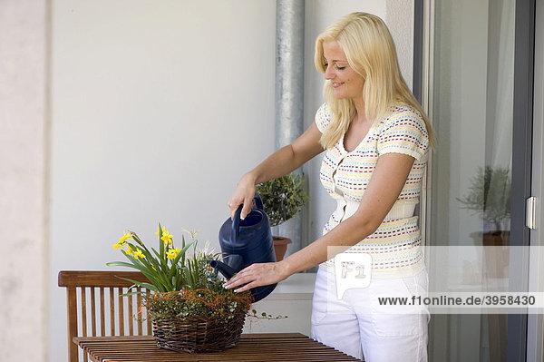 Junge Frau auf einem Balkon beim Blumengießen