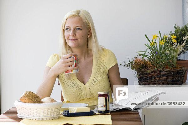 Junge Frau auf einem Balkon  beim Frühstück  lesend