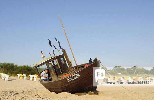 Ein Fischer arbeitet an seinem Fischerboot am Strand im Seebad Heringsdorf  Insel Usedom  Mecklenburg-Vorpommern  Deutschland  Europa