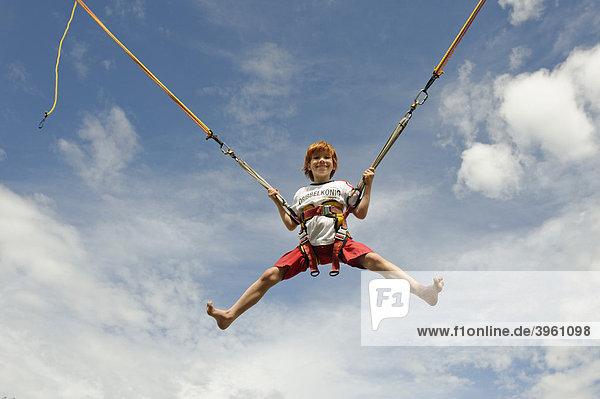 Junge hüpft an einem Bungee Trampolin und fliegt in die Luft