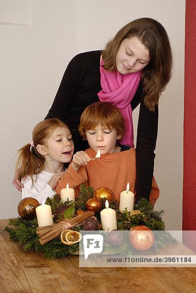 Junge Frau mit Kindern zündet Kerzen an einem Adventskranz an