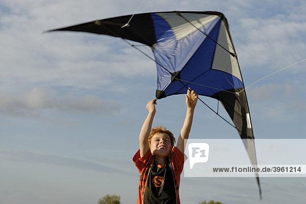 Junge mit Drachen  Kite  Winddrachen  beim Drachensteigen  am Strand