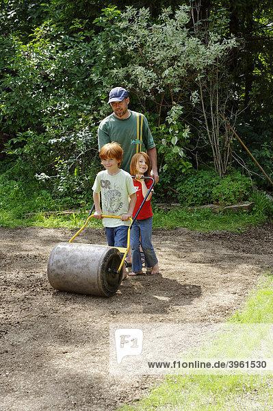 Familie bei der Gartenarbeit  mit der Rasenwalze  Gartenwalze  neuer Rasen  Rasenneuverlegung