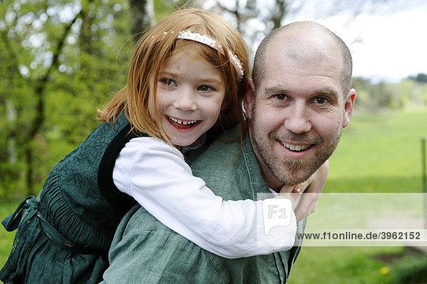 Mädchen turnt auf dem Rücken ihres Vaters
