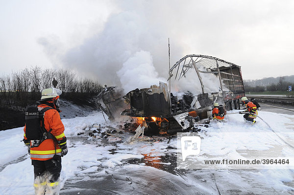 Firefighters during fire-fighting operations involving two trucks after an accident on the motorway A81 between AS Zuffenhausen and Feuerbach  Korntal-Muenchingen  Baden-Wuerttemberg  Germany  Europe