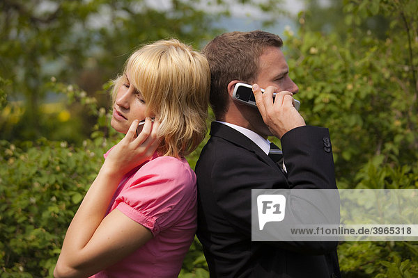 Young woman and a young man standing back to back while talking on mobile phones