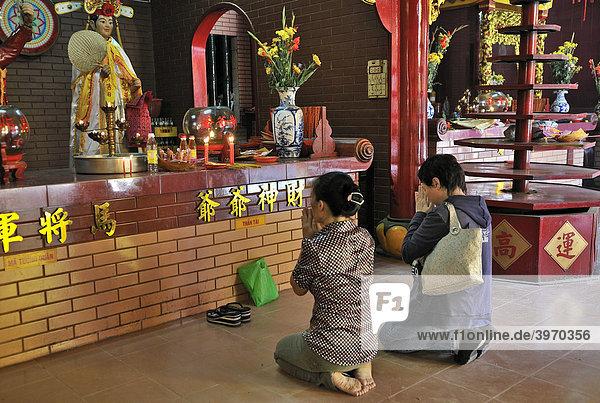 Zwei Frauen knien und beten vor einem Altar mit Buddha  Quan Am Pagode  Ho Chi Minh Stadt  Saigon  Vietnam  Südostasien