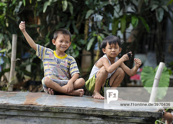 Two children sitting on a wooden roof and playing with thin strings of kites  Vietnam  Asia