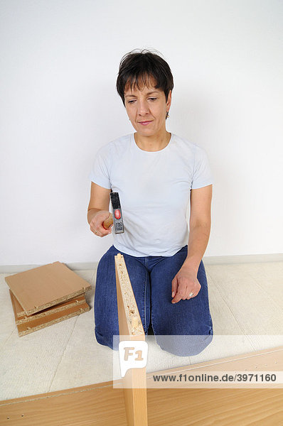 Frau beim Möbel zusammenbauen  Montage Regal-Brett