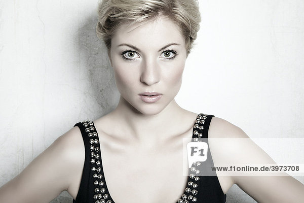 Portrait of a young blond woman in front of a white wall  looking at the viewer