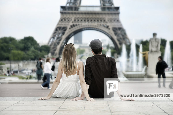 Young couple sitting in front of the Eiffel Tower  Paris  France  Europe