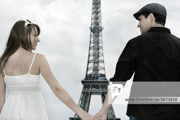 Young couple holding hands in front of the Eiffel Tower  Paris  France  Europe